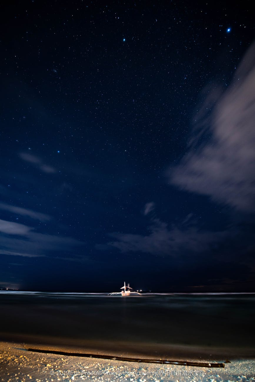 white boat on sea under blue sky during night time