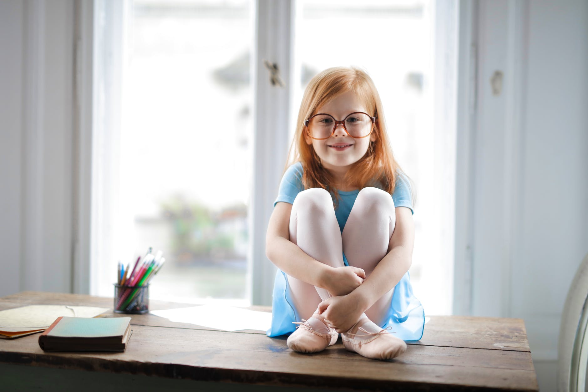 happy cute small girl in glasses sitting on table in light living room